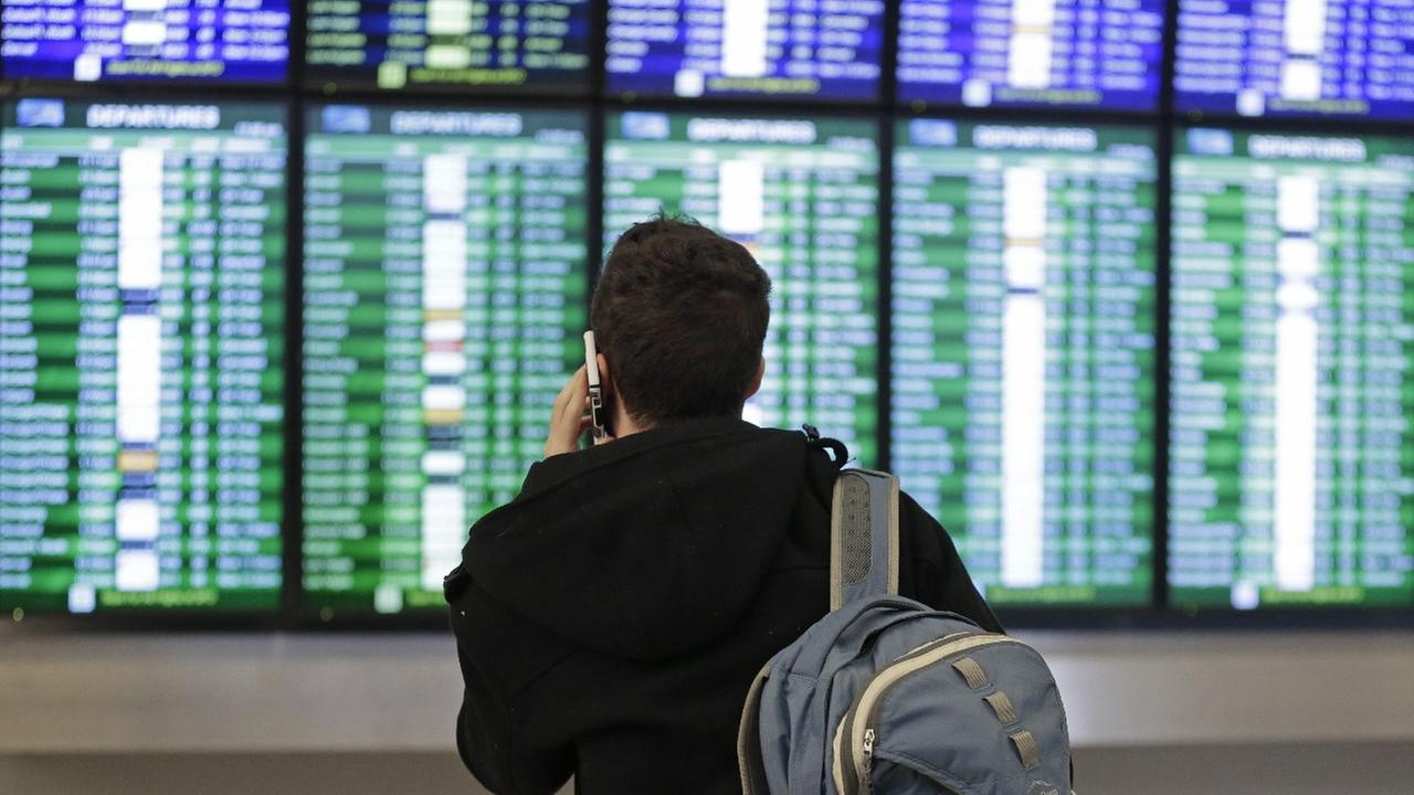A traveler speaks on the phone as he views the arrival and departure board Friday, Jan. 22, 2016, at San Francisco International airport in San Francisco.
