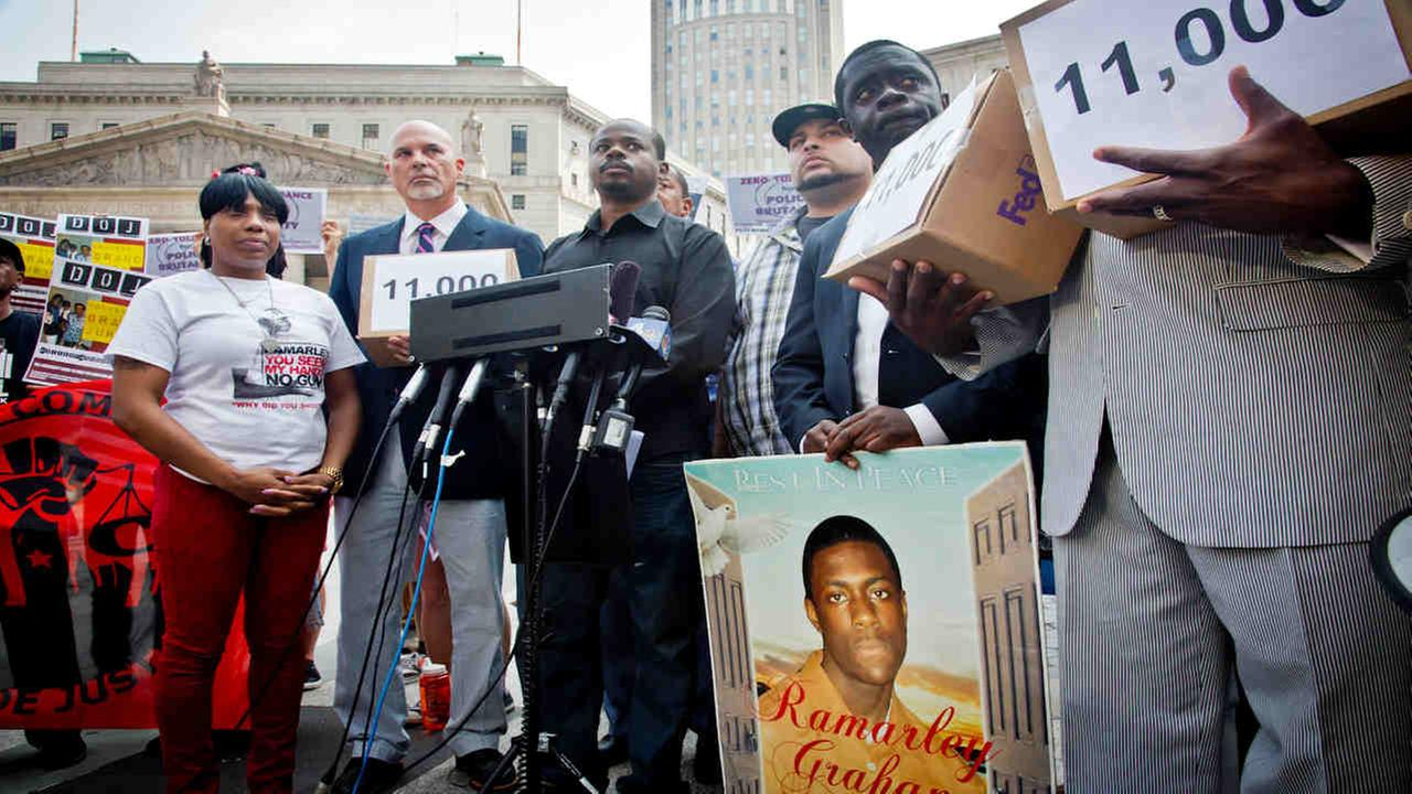 Constance Malcom, left, and Frank Graham, right, the parents of Ramarley Graham, stand in August 2014 with supporters and boxes of petitions at a press conference.