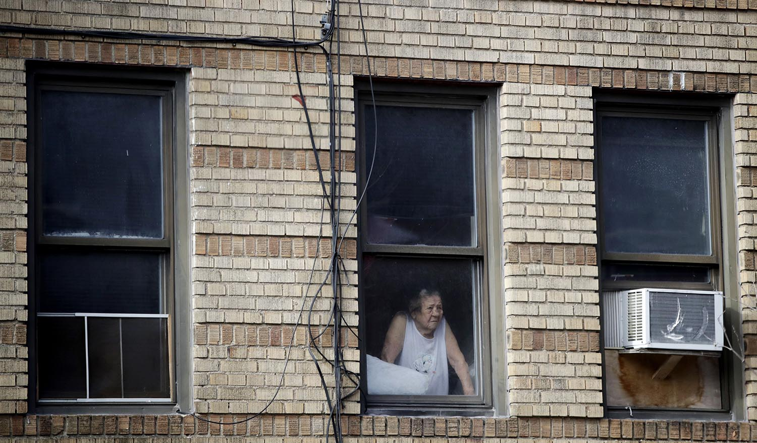 <div class='meta'><div class='origin-logo' data-origin='AP'></div><span class='caption-text' data-credit='AP Photo/Julio Cortez'>A woman looks out the window of a building adjacent to an apartment building where more than 10 people died in fire a day earlier in the Bronx.</span></div>