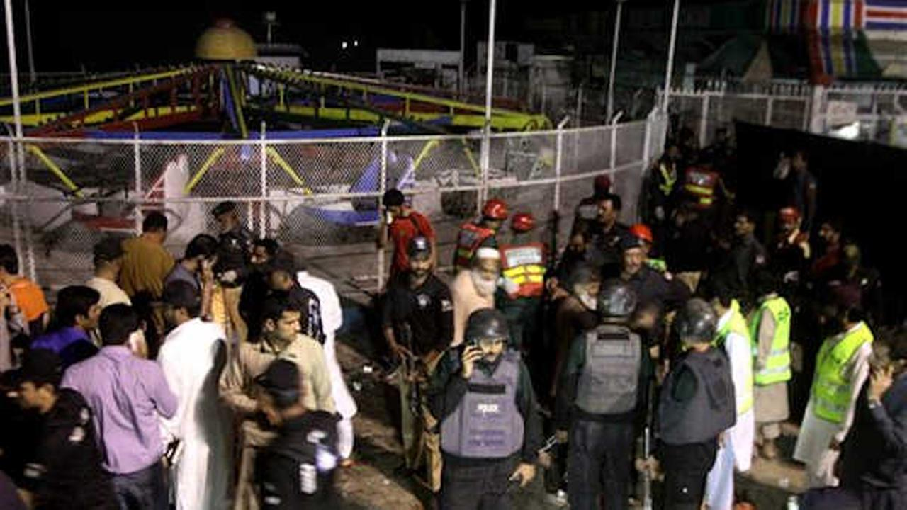 Pakistani police officers and rescue workers gather at the site of bomb explosion in a park in Lahore, Pakistan. (AP Photo/K.M. Chuadary)