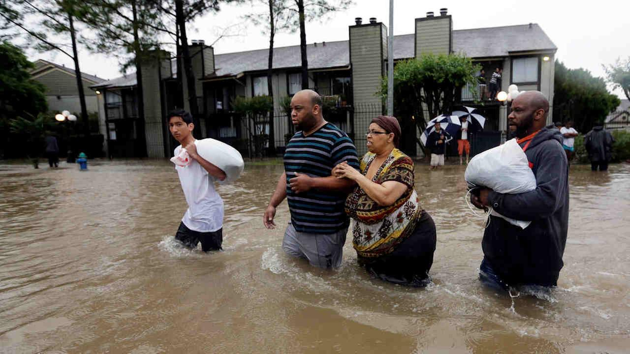 Darius Simon, second from left, helps his mother Carol, evacuate her flooded apartment complex along with his brother Dominique and son, Isaac Hernandez, Monday in Houston.