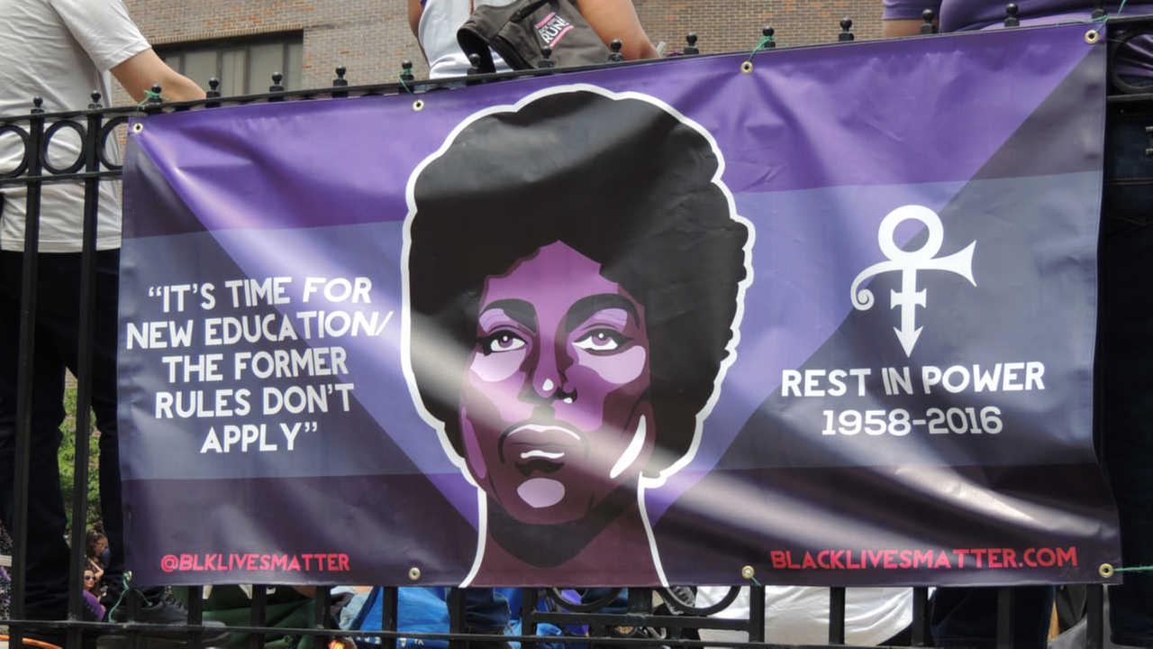 A poster bearing the likeness of the entertainer is attached to a railing at the Prince Born Day Purple People Party? in New York, Saturday, June 4, 2016.
