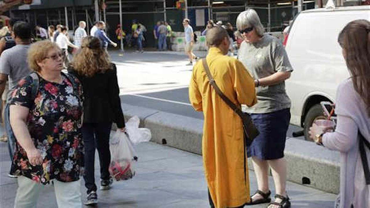 In this Friday, June 24, 2016 photo, a man wearing an orange robe talks with a woman in Times Square.  (AP Photo/Mark Lennihan)