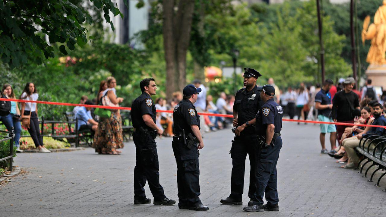 Police officers stand near the borders of a crime scene around the site of an explosion in Central Park, New York, Sunday, July 3, 2016.