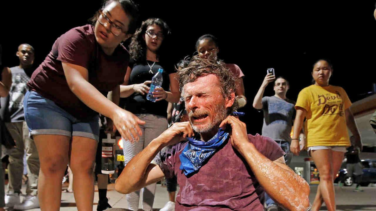 A protester gets help after being knocked to the ground after being sprayed with tear gas by police as marchers numbering nearly 1,000 take to the streets in Phoenix Friday.Ross D. Franklin