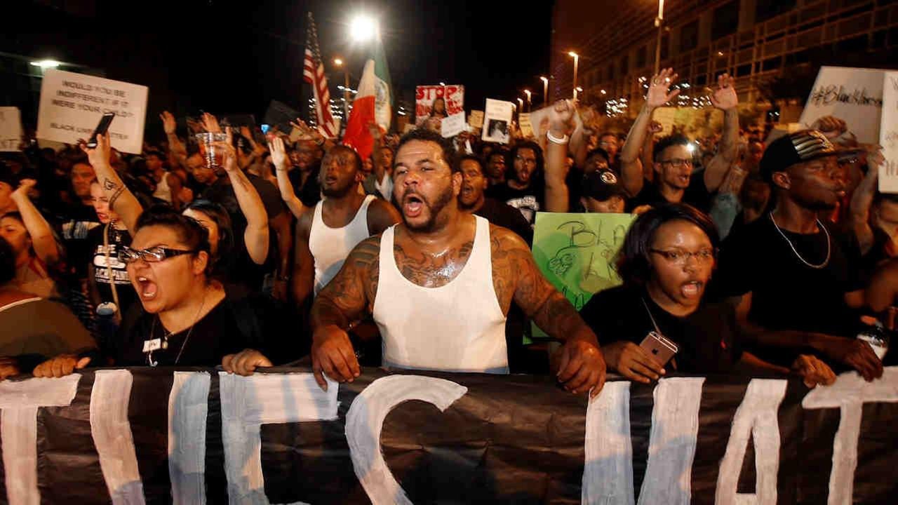 Marchers numbering nearly 1,000 shout in unison as they take to the streets to protest against the recent fatal shootings of black men by police Friday, July 8, 2016, in Phoenix.Ross D. Franklin