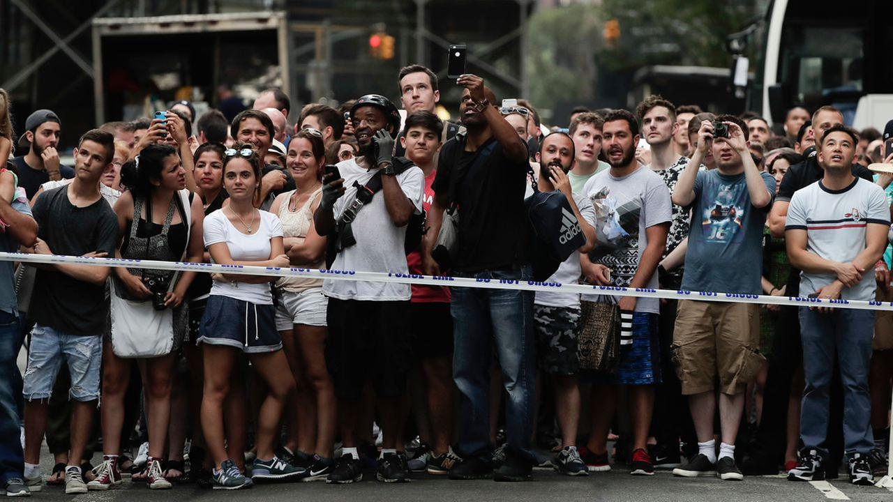 Pedestrians stop to watch as a man scales the all-glass facade of Trump Tower using suction cups Wednesday, Aug. 10, 2016, in New York.AP Photo/Julie Jacobson