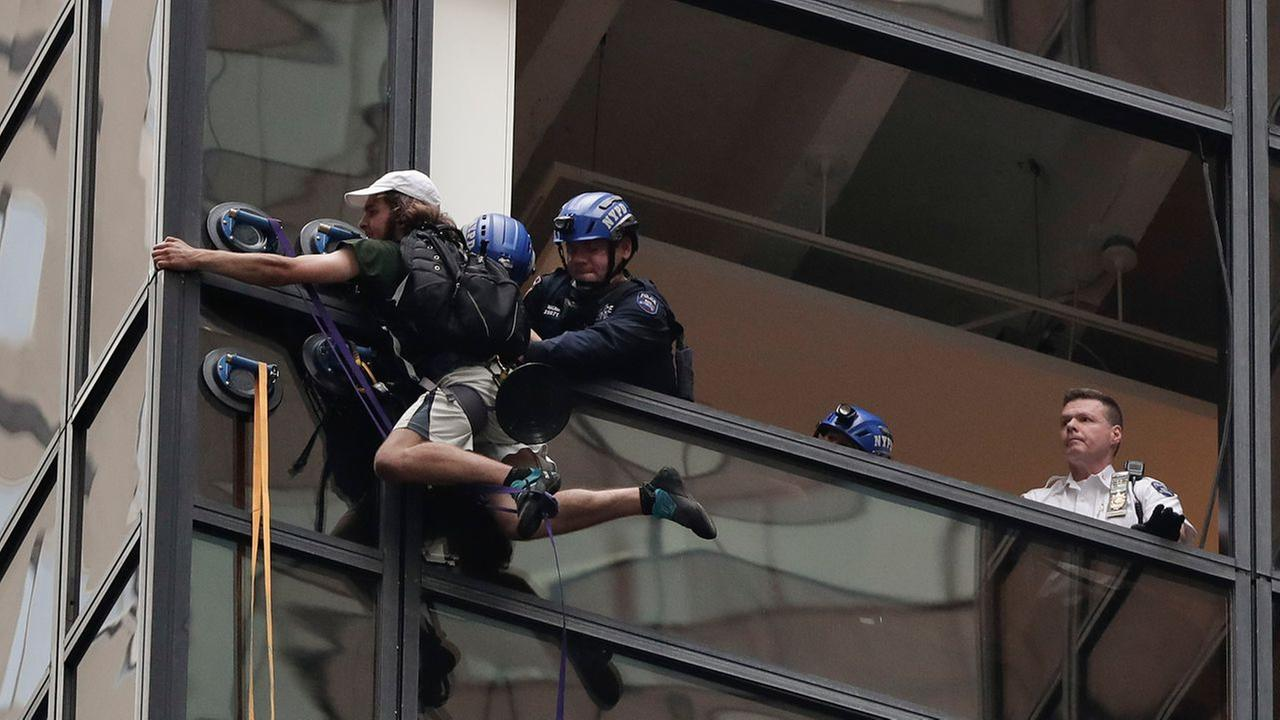 New York Police officers struggle as they pull a man through a window as he scaled the east side of Trump Tower using suction cups, Wednesday, Aug. 10, 2016, in New York. AP Photo/Julie Jacobson