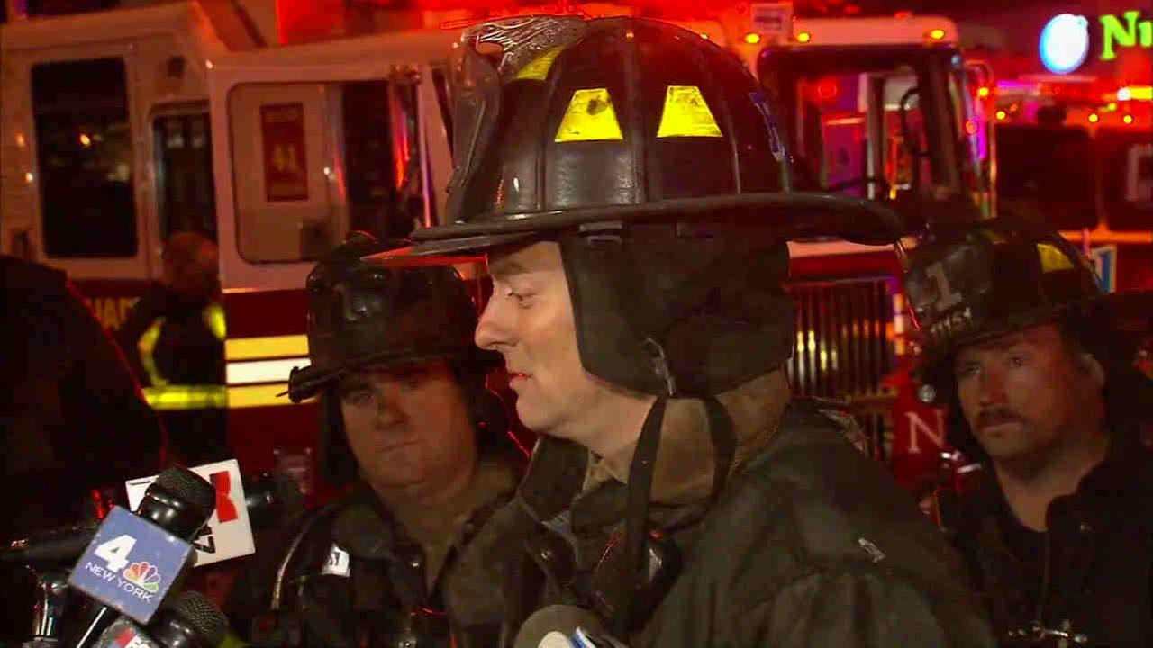A firefighter lowered from the roof of a burning Upper East Side apartment building rescued a man during a six alarm fire that killed one perso