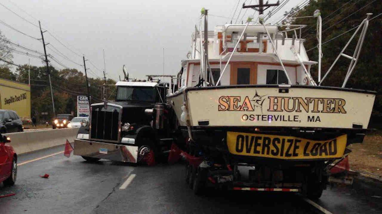 A truck carrying a boat has jackknifed on a New Jersey highway, leading to a fuel spill and big delays as the boat sits on the trailer parked on the roadway.