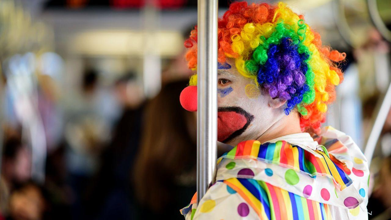 A creepy clown rides the N train from Queens to Manhattan on Sunday, October 30, 2016.
