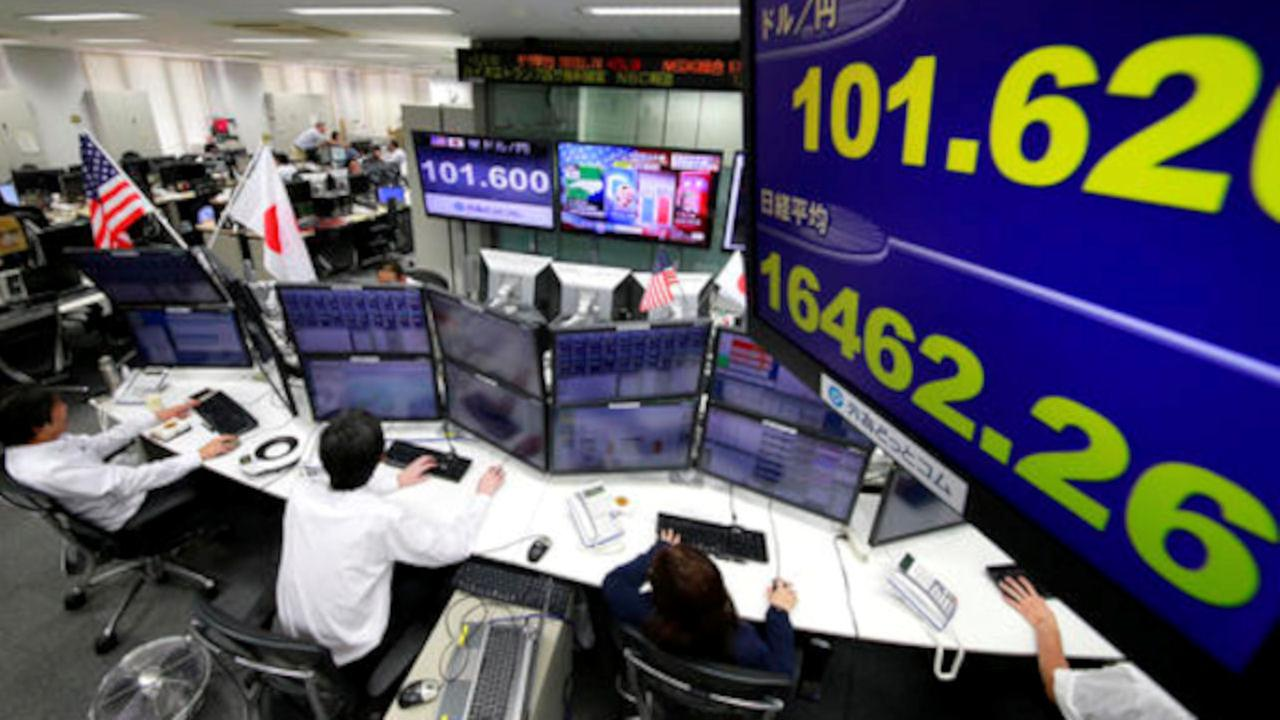 Money traders watch computer screens with the days exchange rate between yen and the U.S. dollar at a foreign exchange brokerage in Tokyo,