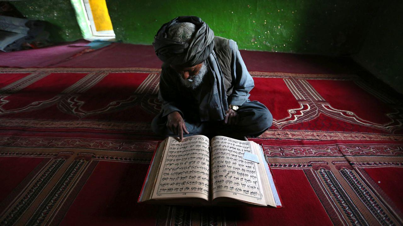 An elderly Afghan man reads the Quran a during of the Islamic month of Ramadan at a mosque in Kabul, Afghanistan, Wednesday, June 15, 2016.