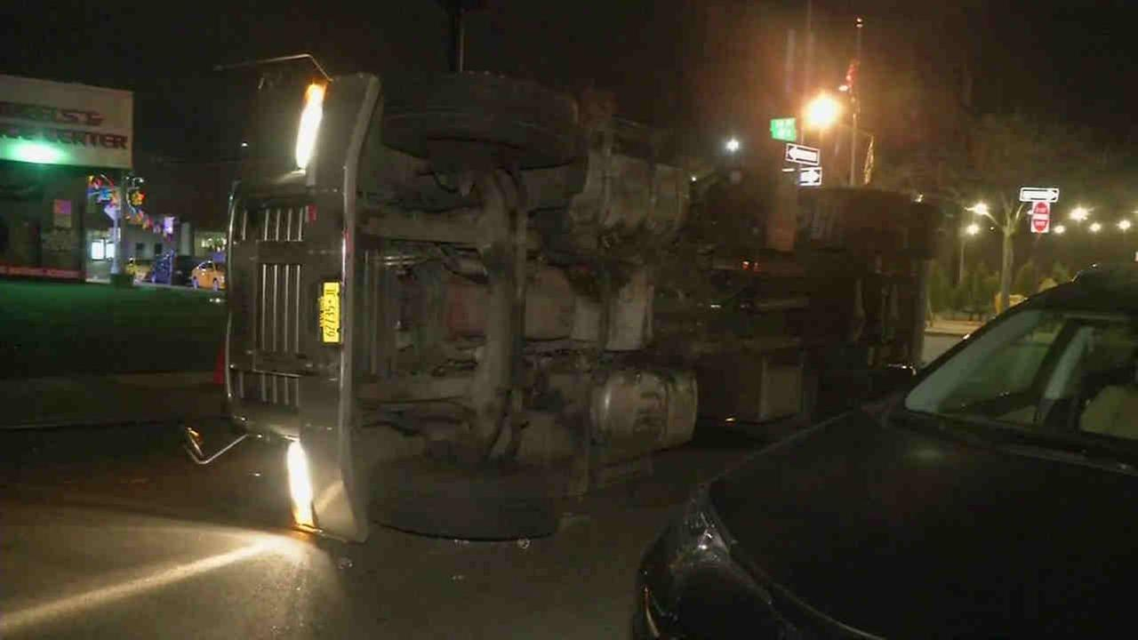 A private sanitation truck overturned on a car in the Astoria section of Queens