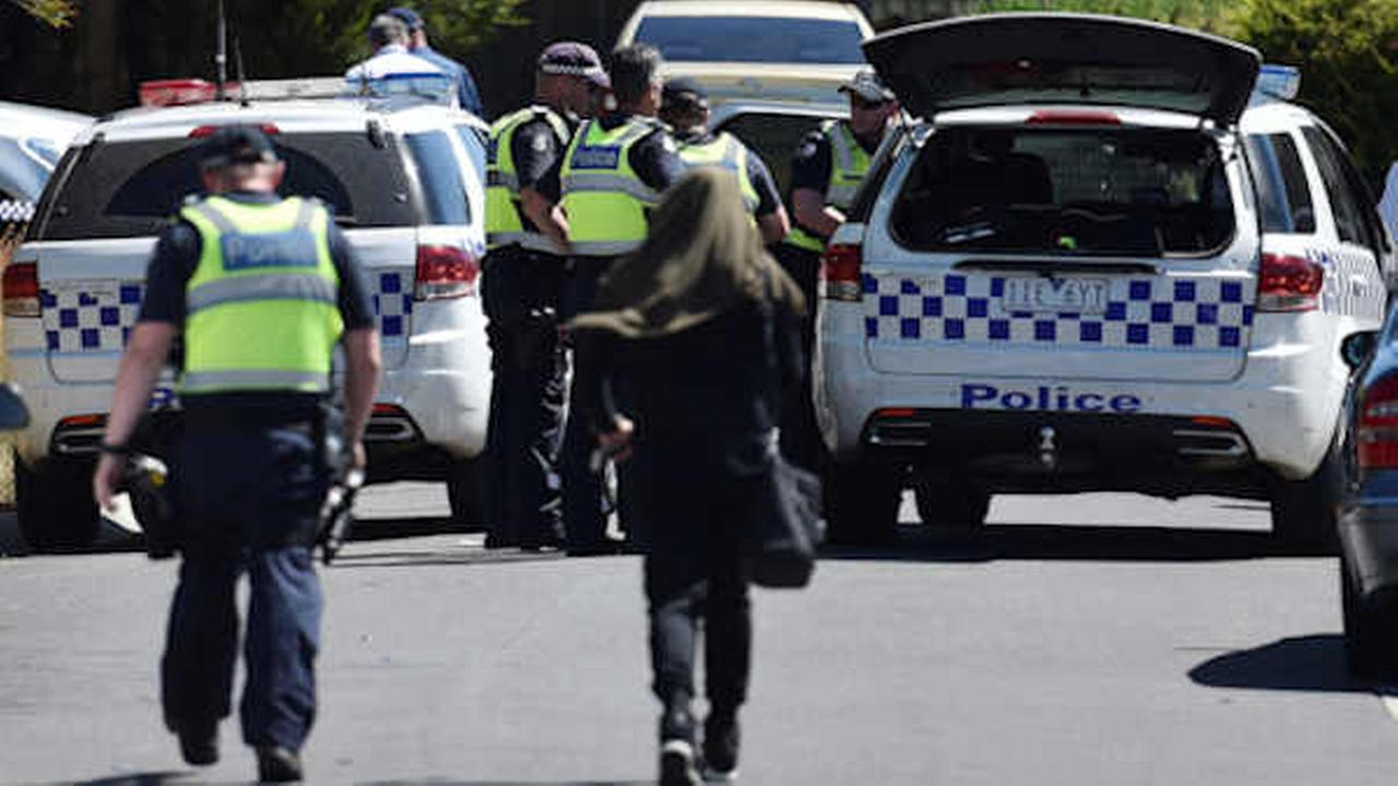Police accompany a woman as they attend the scene where a house was raided at Meadow Heights in Melbourne, Australia, (Julian Smith/AAP Image via AP)