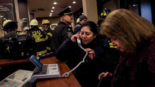 <div class='meta'><div class='origin-logo' data-origin='AP'></div><span class='caption-text' data-credit='Andres Kudacki'>Two women use the phone as firefighters and police gather in the lounge of a building after a fire there got under control on the west side of Manhattan Thursday.</span></div>