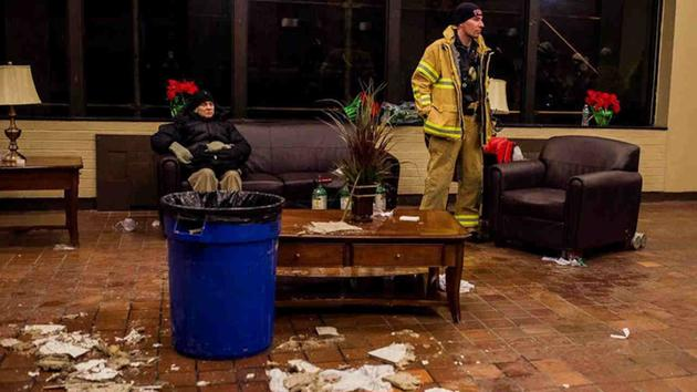 <div class='meta'><div class='origin-logo' data-origin='AP'></div><span class='caption-text' data-credit='Andres Kudacki'>Water leaks from a broken roof as a man rests near a firefighter in the lounge of a high-rise building after a fire is under control on the west side Thursday.</span></div>