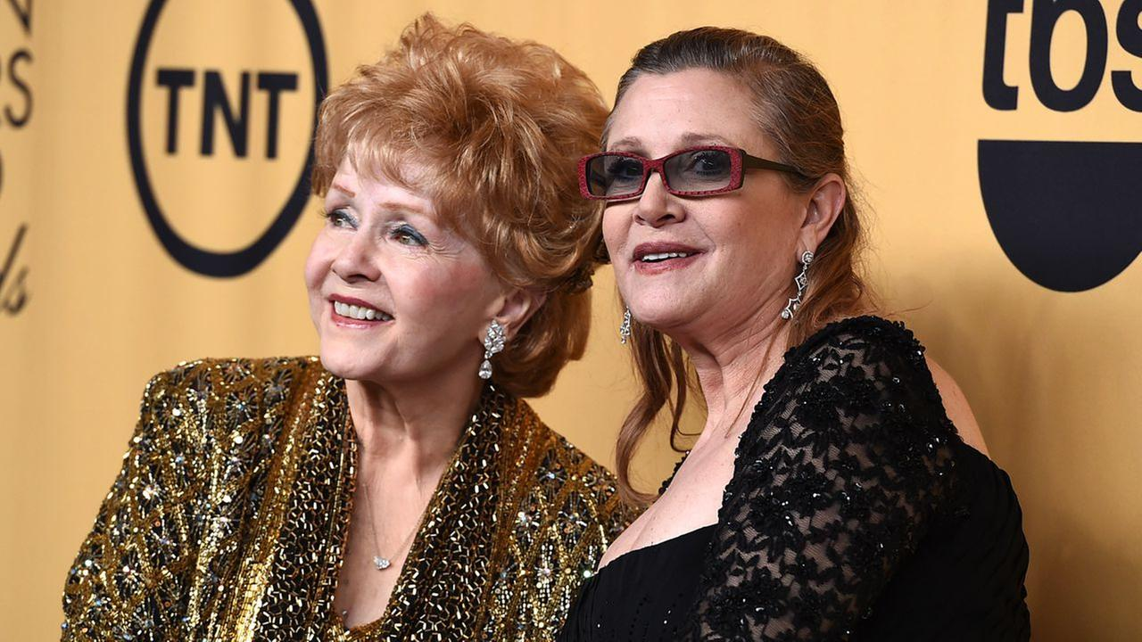 Debbie Reynolds, winner of the Screen Actors Guild lifetime award, left, and Carrie Fisher pose in the press room at the 21st annual Screen Actors Guild Awards on Jan. 25, 2015.