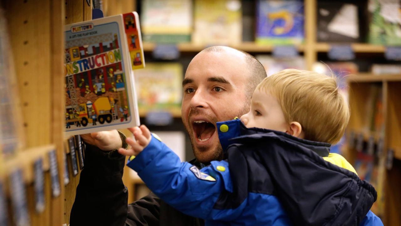 Customer Michael Wallenfels looks at childrens books with his son Henry, 2, at the opening day for Amazon Books Tuesday, Nov. 3, 2015, in Seattle.