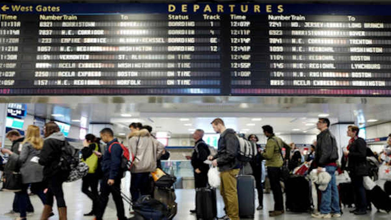Passengers stand beneath an electronic signboard in Penn Station as they wait to board a train, Sunday, Nov. 27, 2016.  (AP Photo/Mark Lennihan)