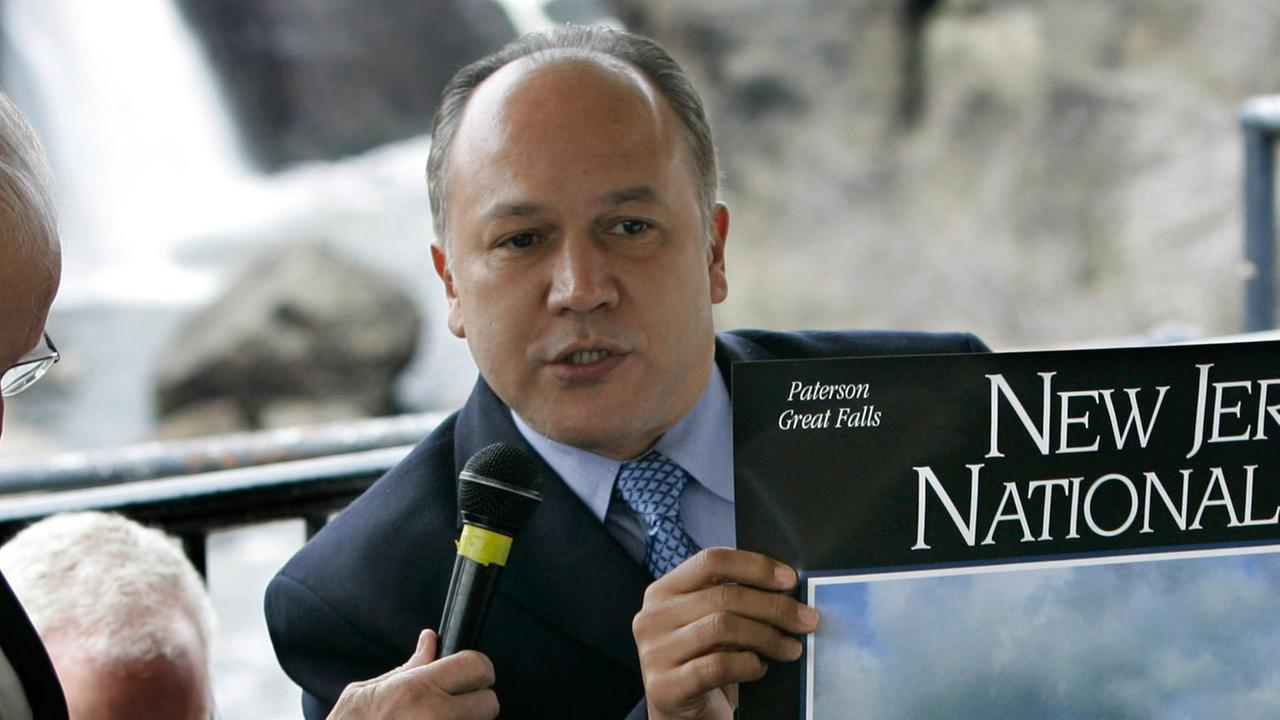 Jose Joey Torres, center, Mayor of Paterson, N.J., holds up a National Park poster of the Great Falls during a ceremony in Paterson, N.J., Wednesday, April 15, 2009.