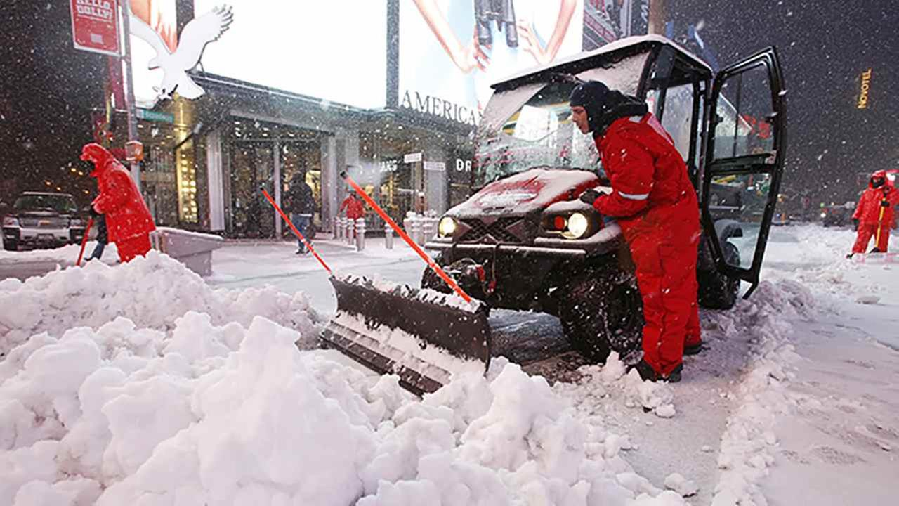 Men shovel snow as a storm swept through Times Square, Tuesday in New York.