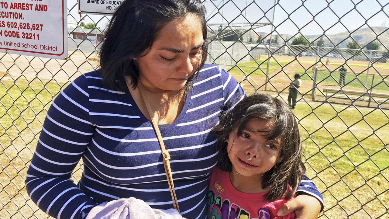 Elizabeth Barajas hugs her daughter, Marissa Perez, 9, following their reunion as Marissa recounted her experiences being in the classroom in which her teacher was shot to death.