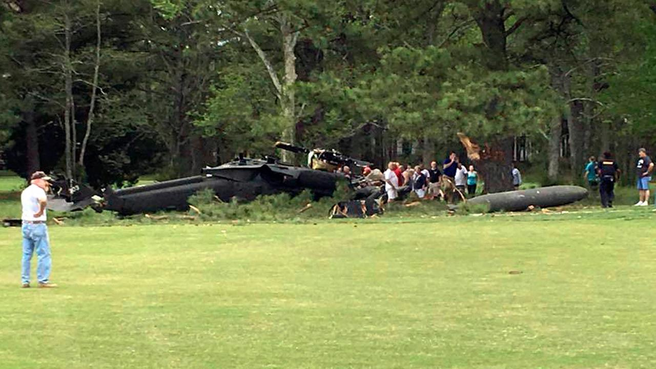 People examine an Army UH-60 helicopter from Fort Belvoir, Va., after it crashed at the Breton Bay Golf and Country Club (Rebecca Updegrave Cline via AP)