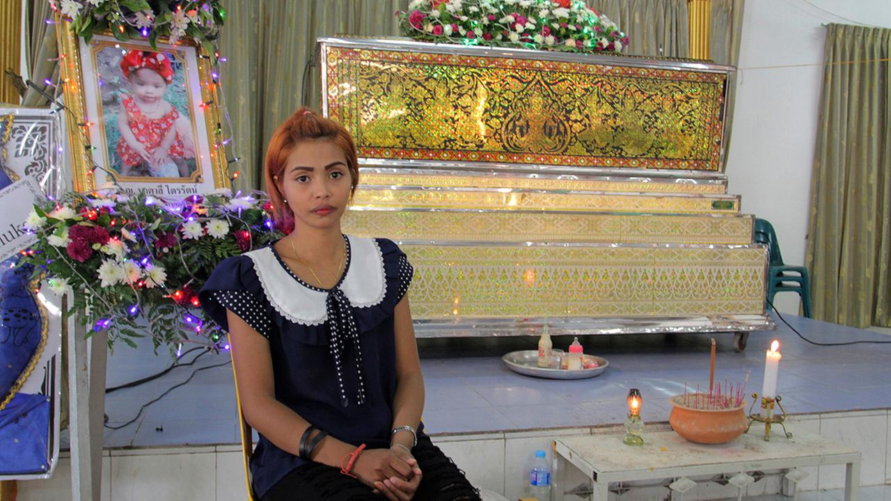 Chiranut Trairat, mother of an 11-month-old baby girl, sits in front of her daughters coffin at Si Sunthon temple in Phuket, Thailand, Wednesday, April 26, 2017.
