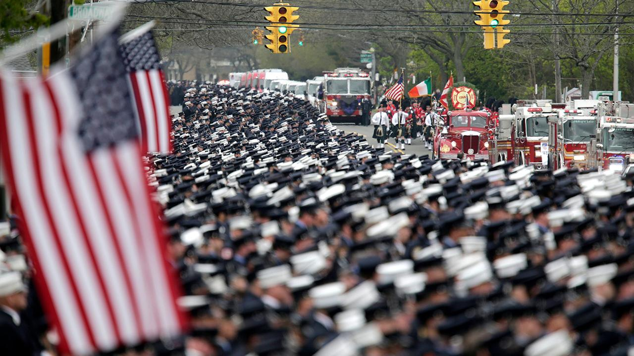 Firefighters stand at attention as the funeral procession for William Tolley arrives at the church in Bethpage, N.Y., Thursday, April 27, 2017.