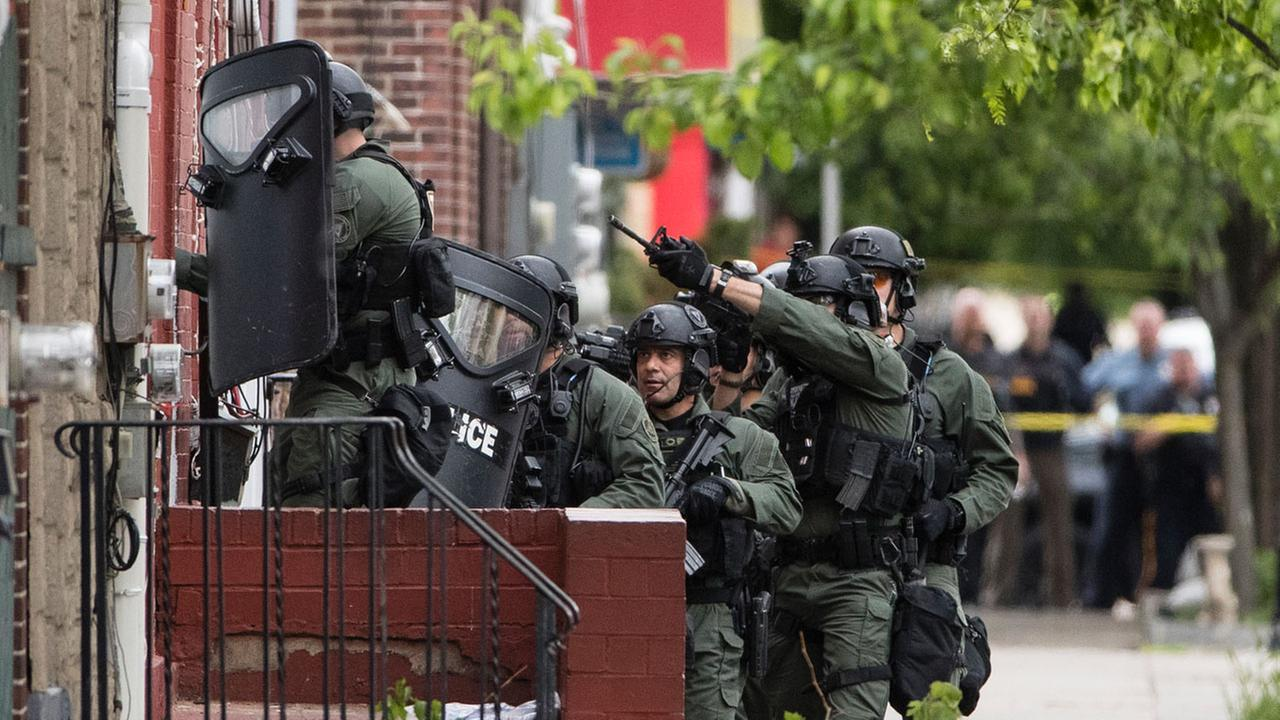 In this Wednesday, May 10, 2017 photo police officers move closer to a standoff with a man in a home in Trenton, N.J. Police said they are trying to negotiate with the suspect afte