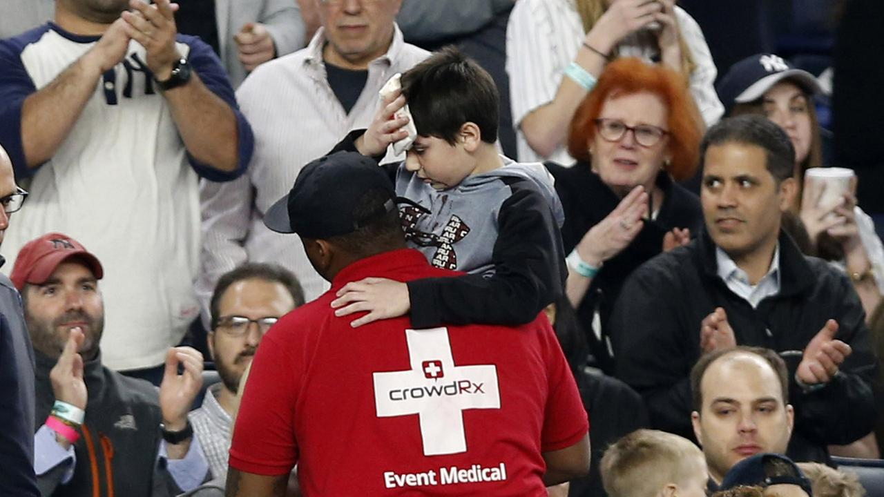 Fans applaud as a medical employee carries an injured youngster from the stands after the boy was hit in the head by a piece the Yankeess Chris Carters bat that split.