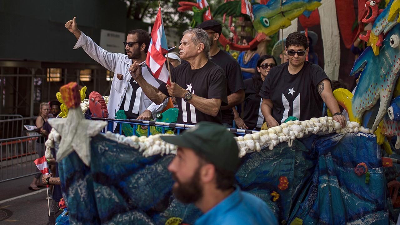 Puerto Rican activist Oscar Lopez Rivera, center, rides in a float along 5th Ave. during the National Puerto Rican Day Parade Sunday, June 11, 2017 in New York. (AP Photo/Andres Ku