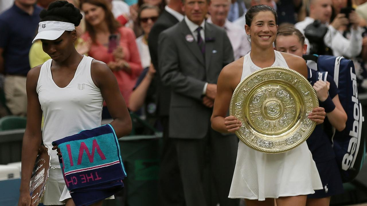 Venus Williams of the United States, left leaves with her runner-up trophy from Centre Court after her defeat by Spains Garbine Muguruza, right  (AP Photo/Tim Ireland)