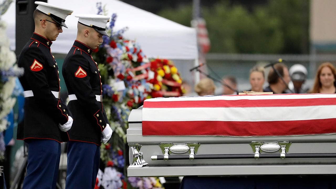 Marines stand guard next to a casket containing the body of Cpl. Dan Baldassare, a Marine killed in a military plane crash in Mississippi, during funeral services in Colts Neck