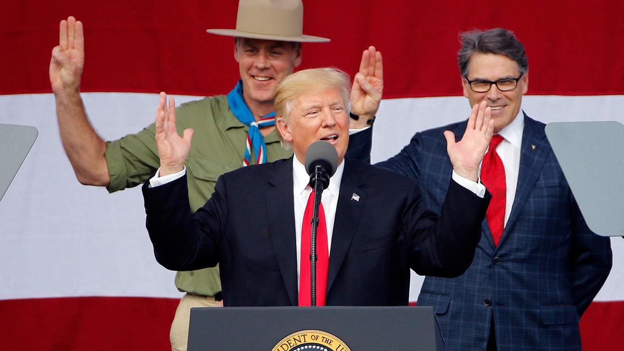 President Donald Trump, front left, gestures as former boys scouts, Interior Secretary Ryan Zinke, left, Energy Secretary Rick Perry, watch at the 2017 National Boy Scout Jamboree.