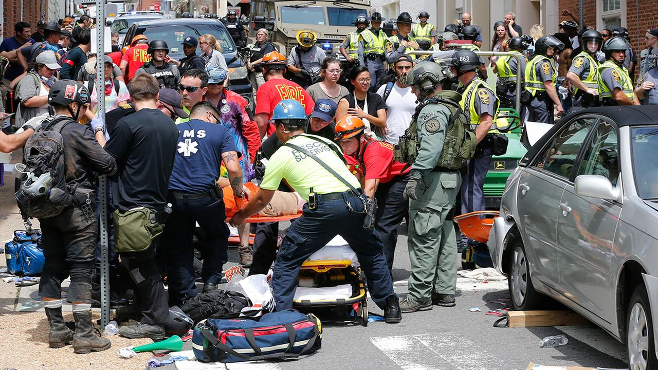 Rescue personnel help injured people after a car ran into a large group of protesters after an white nationalist rally (AP Photo/Steve Helber)