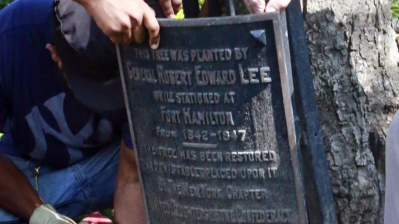 Workers remove one of two plaques honoring Confederate Gen. Robert E. Lee on the property of St. Johns Episcopal Church, Wednesday Aug. 16, 2017.