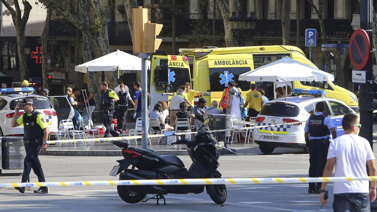 Injured people are treated in Barcelona, Spain, Thursday, Aug. 17, 2017 after a white van jumped the sidewalk in the historic Las Ramblas district, crashing into a crowd.