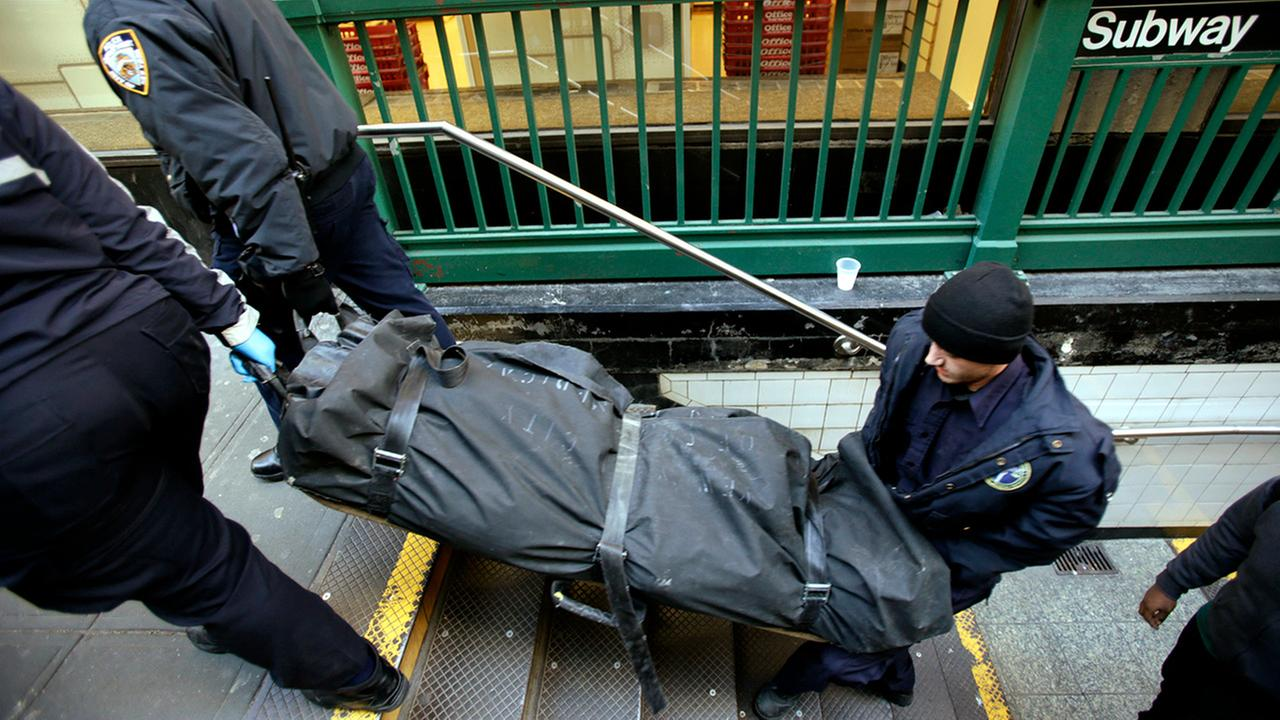 In this Jan. 22, 2013 file photo, a police officer and medical examiner personnel carry a body out of the Times Square subway station