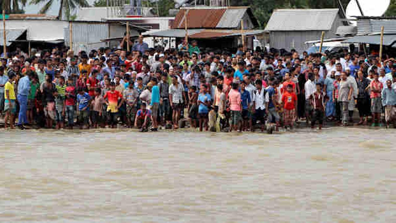Bangladeshi people gather on the banks of the River Padma after a passenger ferry capsized in Munshiganj district, Bangladesh, Monday, Aug. 4, 2014.