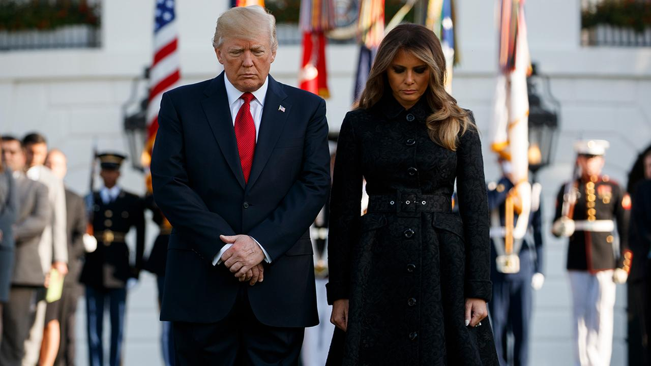 President Donald Trump and first lady Melania Trump stand for a moment of silence to mark the anniversary of the Sept. 11 terrorist attacks, on the South Lawn of the White House,