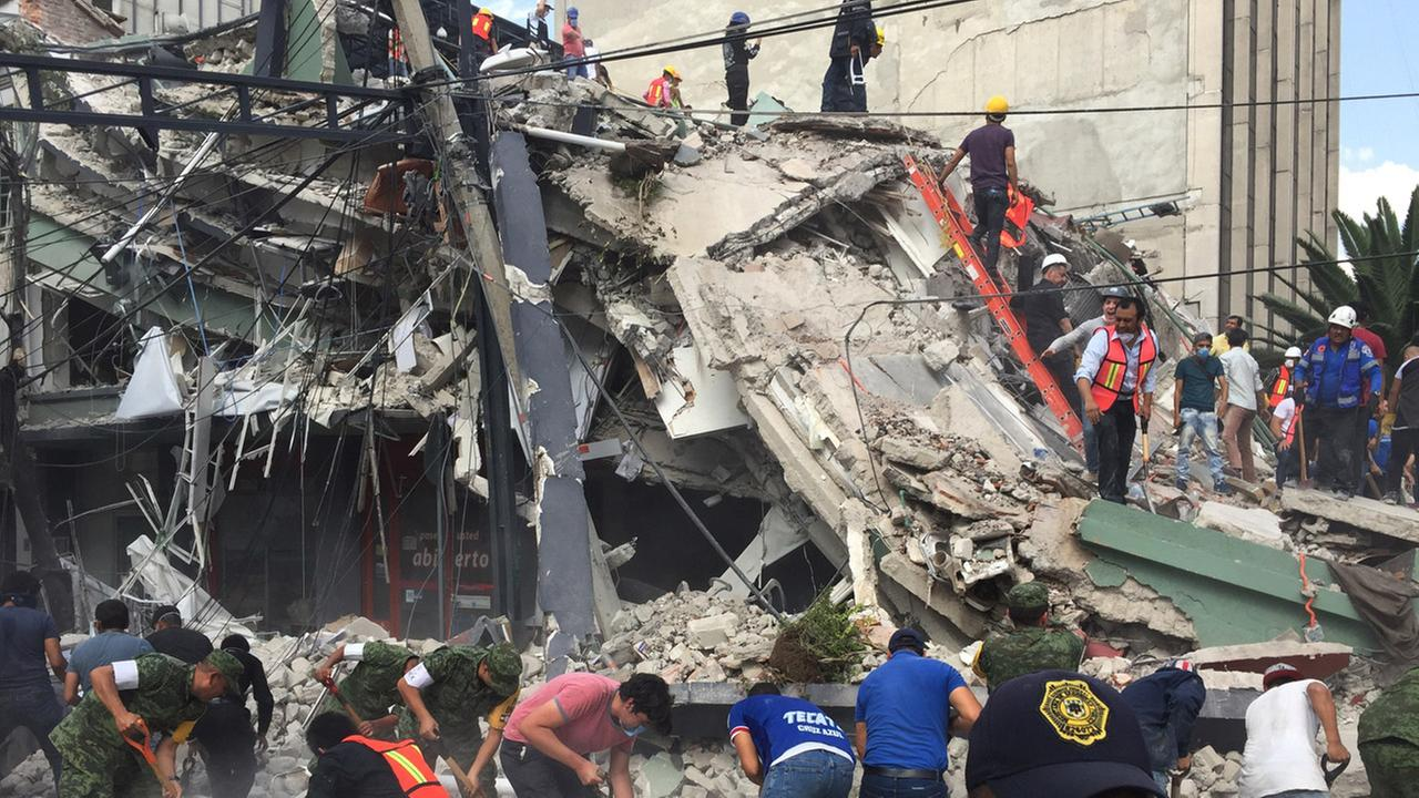People search for survivors in a collapsed building in the Roma neighborhood of Mexico City, Tuesday, Sept. 19, 2017.