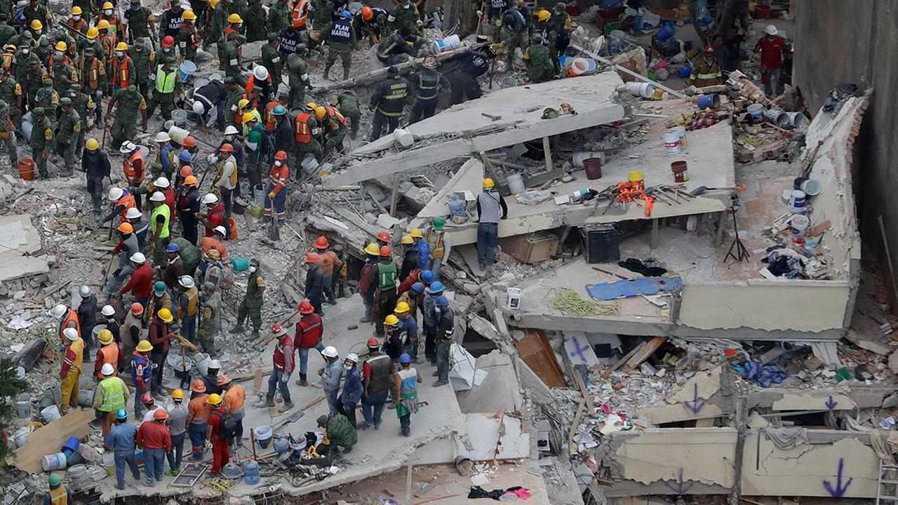 Rescue workers search for people trapped inside a collapsed building in the Del Valle area of Mexico City.  (AP Photo/Rebecca Blackwell)