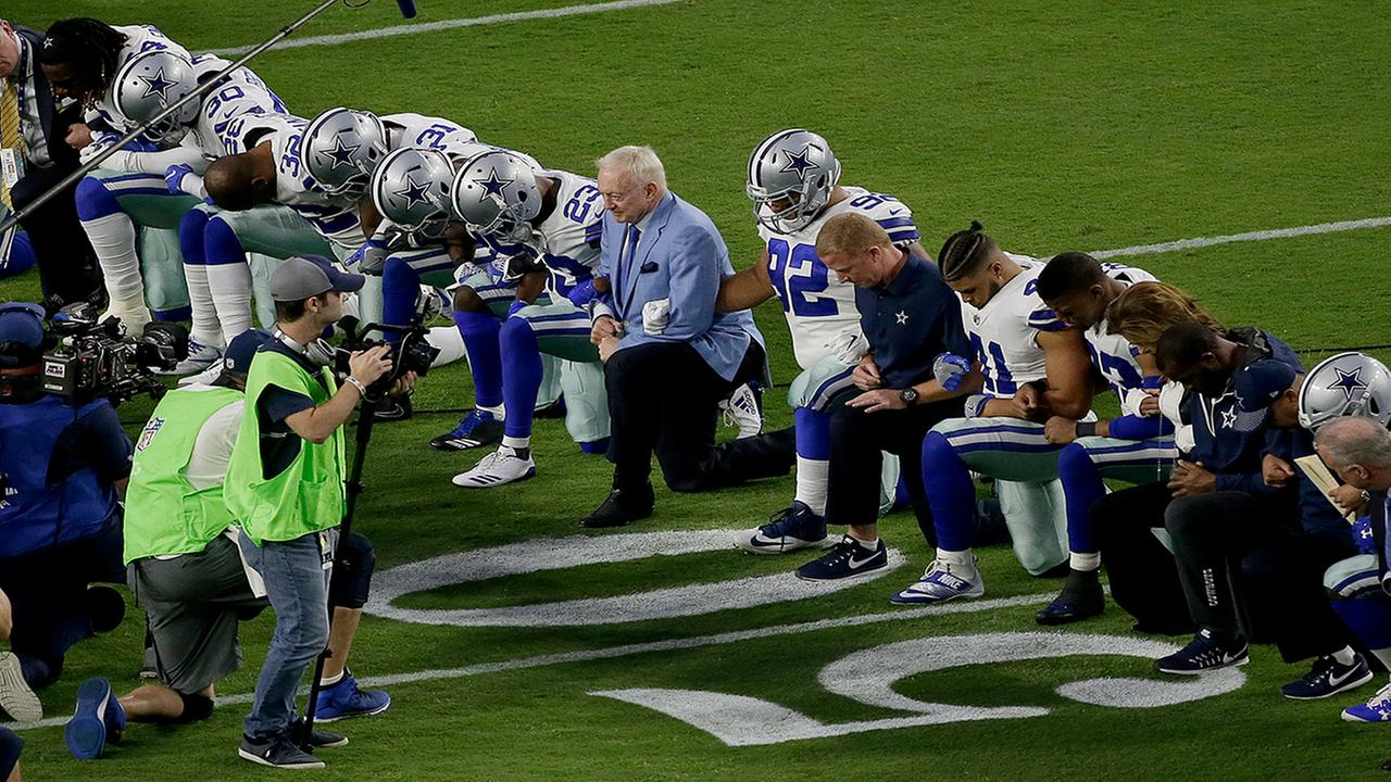 The Dallas Cowboys, led by owner Jerry Jones, center, take a knee prior to the national anthem prior to an NFL football game against the Arizona Cardinals