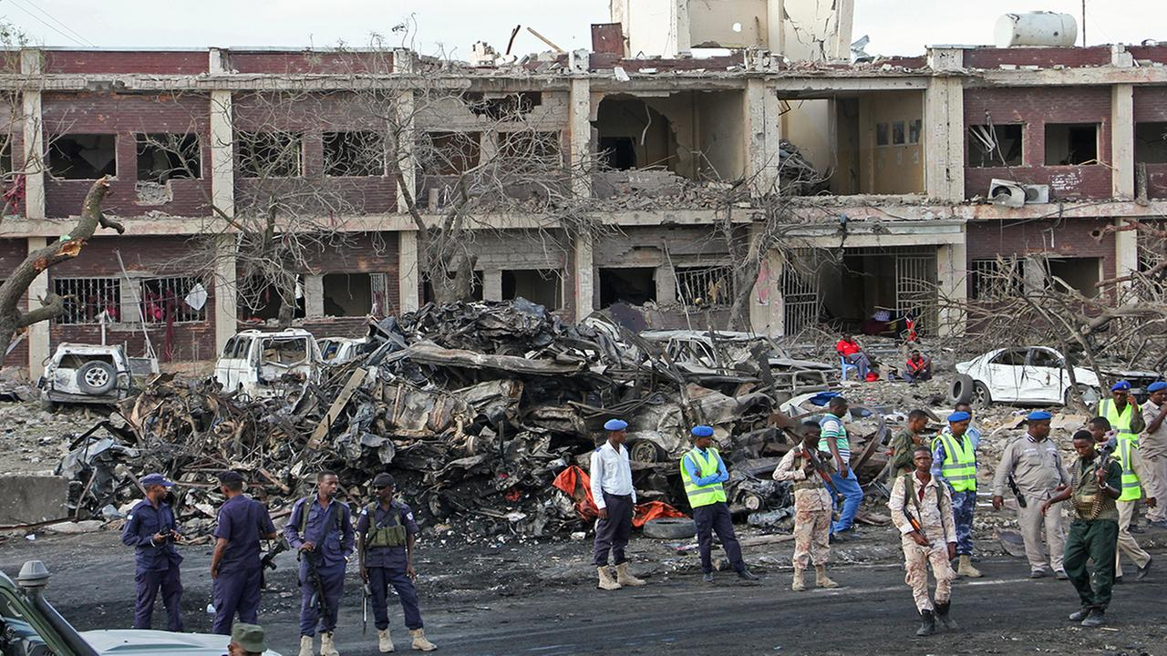 Somali security forces and others gather and search for bodies near destroyed buildings at the scene of Saturdays blast, in Mogadishu, Somalia