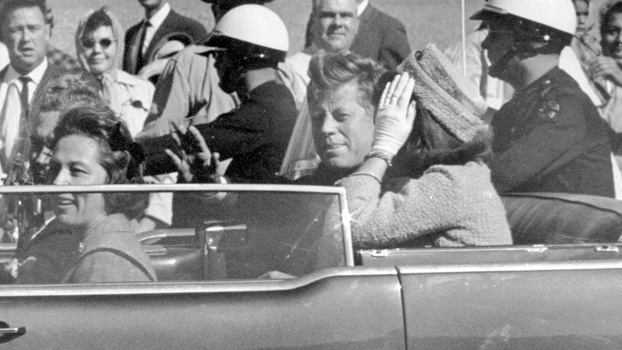 In this Nov. 22, 1963 file photo, President John F. Kennedy waves from his car in a motorcade in Dallas.  (AP Photo/Jim Altgens, File)