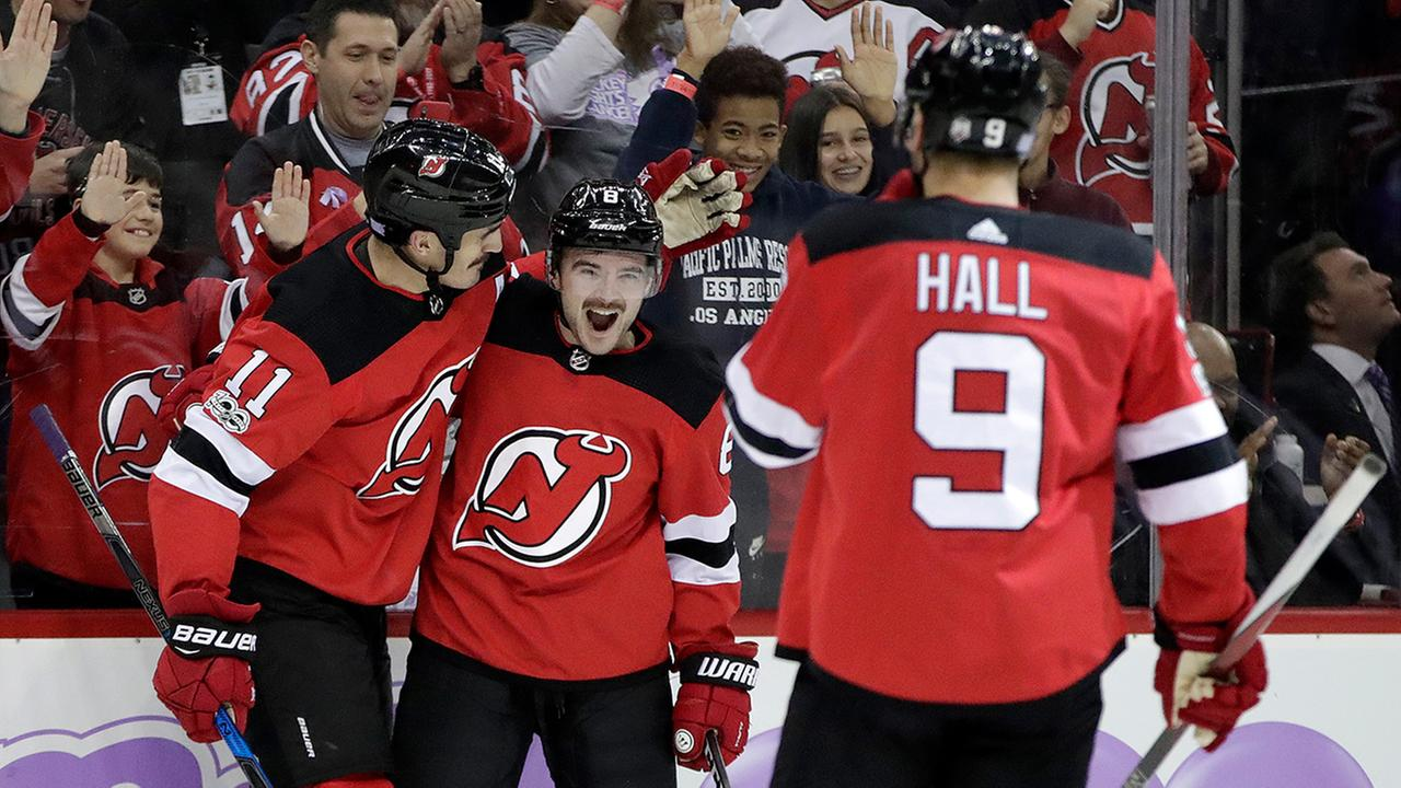 New Jersey Devils defenseman Will Butcher, center, center Brian Boyle, left, and left wing Taylor Hall (9) celebrate Boyles goal against Vancouver. (AP Photo/Julio Cortez)