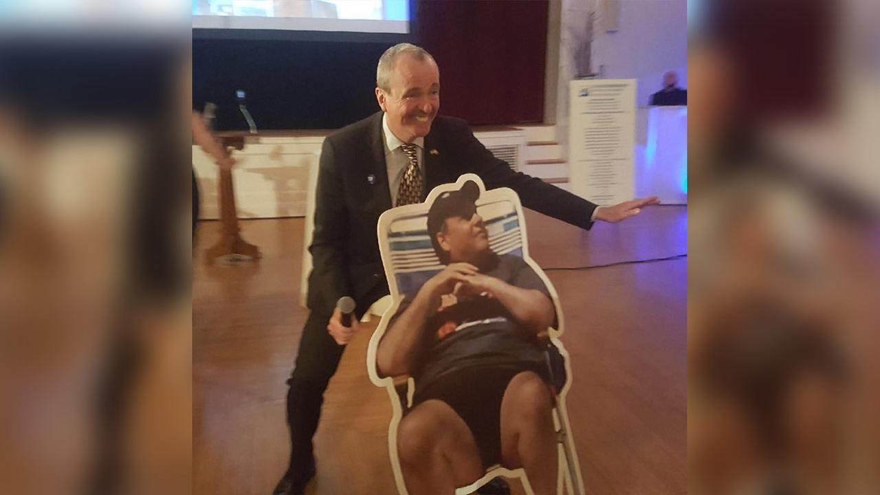 Gov.-elect Phil Murphy poses next to cutout of Gov. Chris Christie on beach