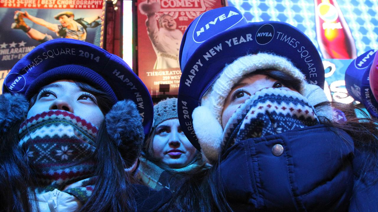 Bundled against the cold, Yuri Asano, left, and her sister Mami Asano, right, both from Aichi, Japan, take part in the New Years Eve festivities Tuesday Dec. 31, 2013.